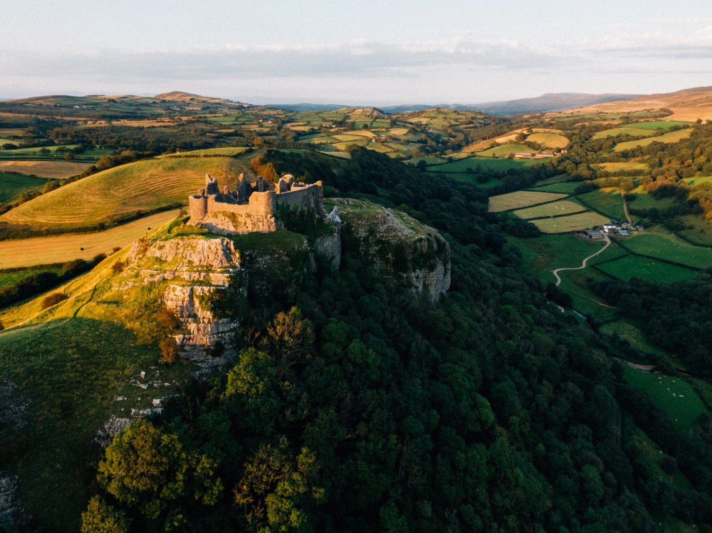a castles on a hill surrounded by green rolling hills in Wales.